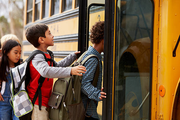 elementary school kids climbing on to a school bus - school bus stock photos and pictures