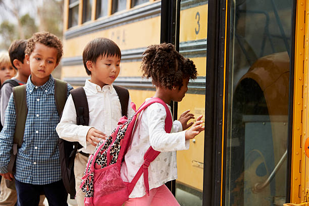 elementary school kids climbing on to a school bus - getting on stock photos and pictures