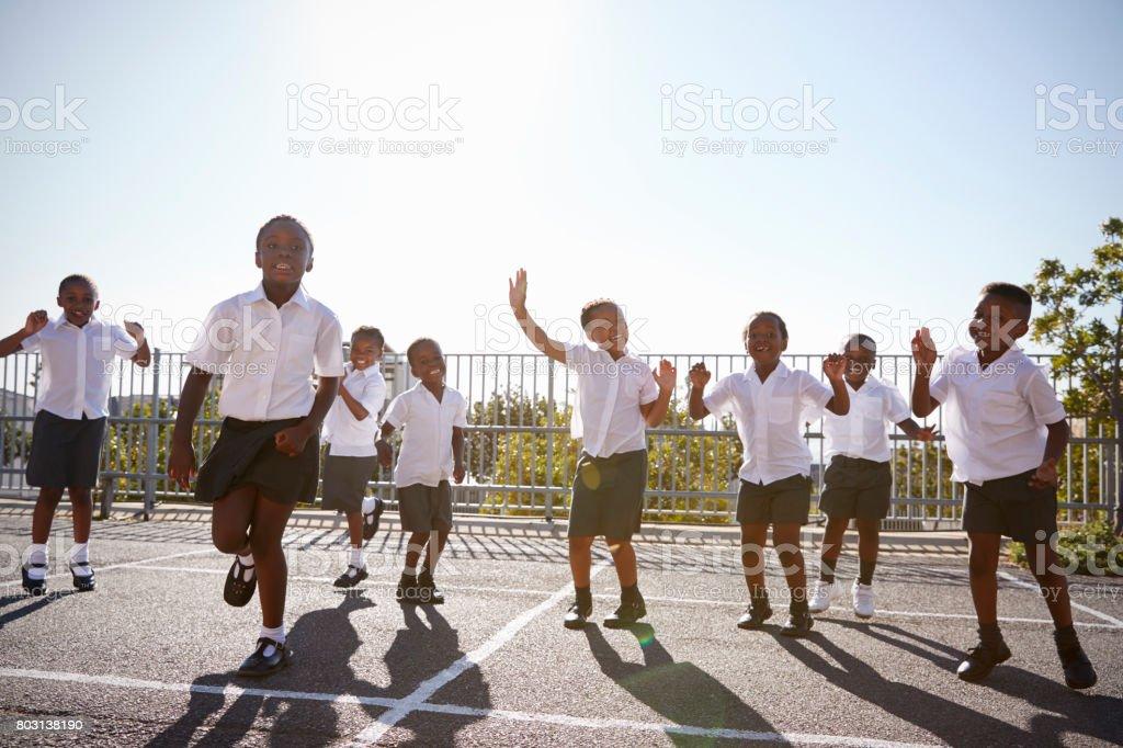 Elementary school kids having fun in school playground stock photo