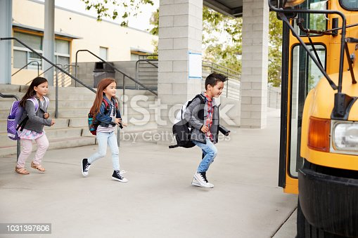 1031397608 istock photo Elementary school kids leaving school to get the school bus 1031397606