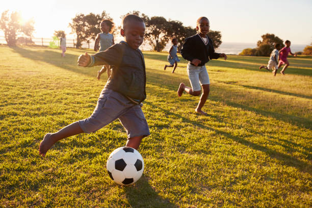 Elementary school kids playing football in a field stock photo