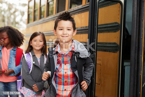 1031397608 istock photo Elementary school kids queueing for the school bus 1031397098