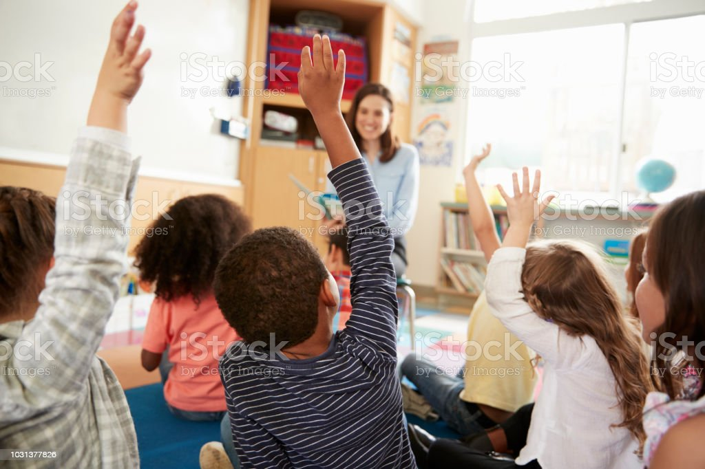 Elementary school kids raising hands to teacher, back view foto stock royalty-free