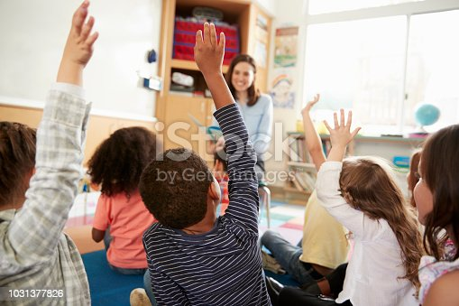 istock Elementary school kids raising hands to teacher, back view 1031377826