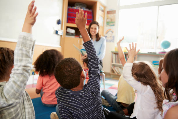 Elementary school kids raising hands to teacher, back view Elementary school kids raising hands to teacher, back view elementary school stock pictures, royalty-free photos & images