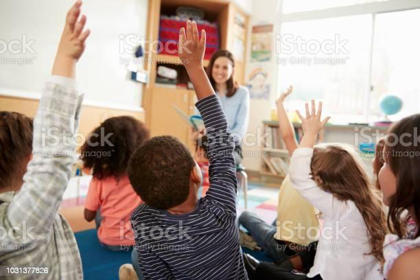 Dzieci Ze Szkoły Podstawowej Podnoszące Ręce Do Nauczyciela Widok Z Tyłu - zdjęcia stockowe i więcej obrazów Budynek szkolny