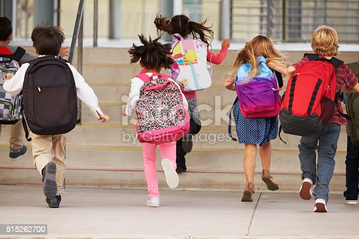 istock Elementary school kids running into school, back view 515262700