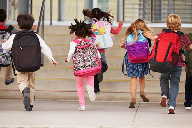 bambini correre nella scuola elementare scuola, vista posteriore - cartella scolastica foto e immagini stock