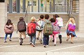 istock Elementary school kids running into school, back view 515262858