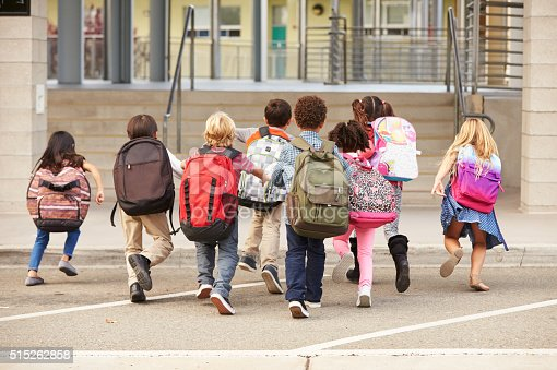 istock Elementary school kids running into school, back view 515262858