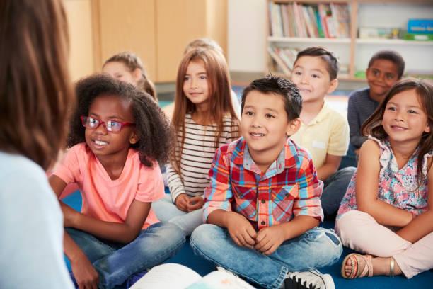 Elementary school kids sit on floor looking up at teacher stock photo