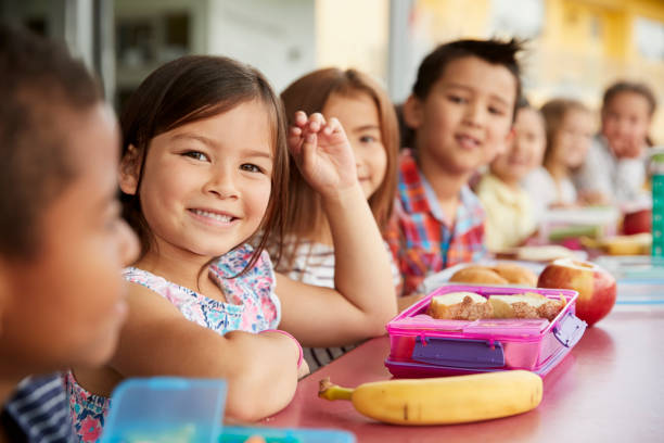 Elementary school kids sitting a table with  packed lunches stock photo