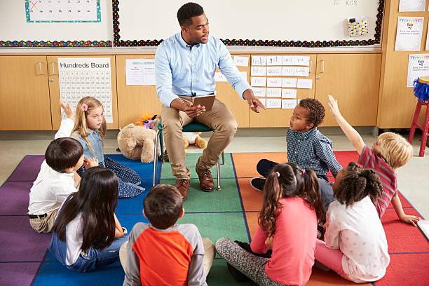 Elementary school kids sitting around teacher in a lesson stock photo