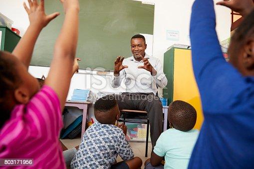 istock Elementary school kids sitting on floor listening a teacher 803171956