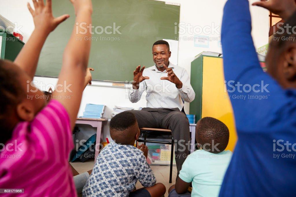 Elementary school kids sitting on floor listening a teacher stock photo
