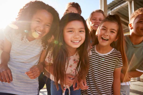 escuela primaria niños sonriendo a la cámara en el recreo - escuela primaria fotografías e imágenes de stock