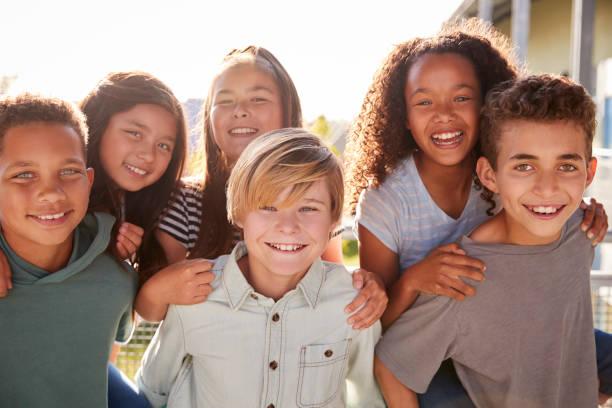 grundschule kinder kamera lächeln und während der schulferien - kind vor der pubertät stock-fotos und bilder