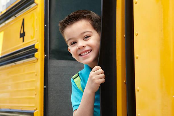 escuela primaria alumno boarding bus - autobuses escolares fotografías e imágenes de stock
