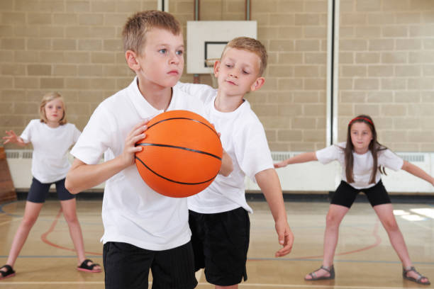 Elementary School Pupils Playing Basketball In Gym stock photo