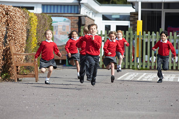 elementary school pupils running in playground - recess stock pictures, royalty-free photos & images