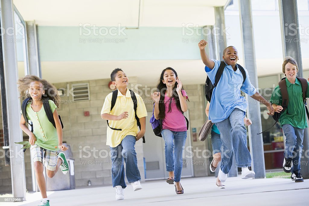 Elementary school pupils running outside royalty-free stock photo
