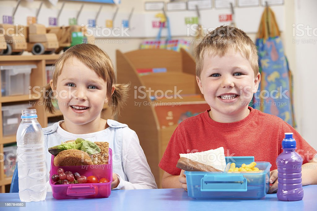 Elementary School Pupils With Healthy And Unhealthy Lunch Boxes stock photo