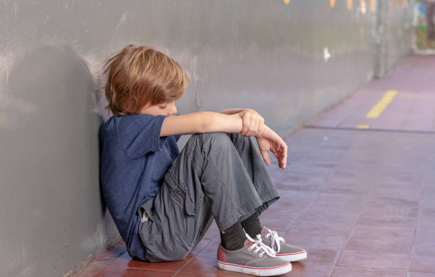 Elementary School. Sad little boy oppressing in the schoolyard. Bullying concept Elementary School. Sad little boy oppressing in the schoolyard. Bullying concept. poverty stock pictures, royalty-free photos & images