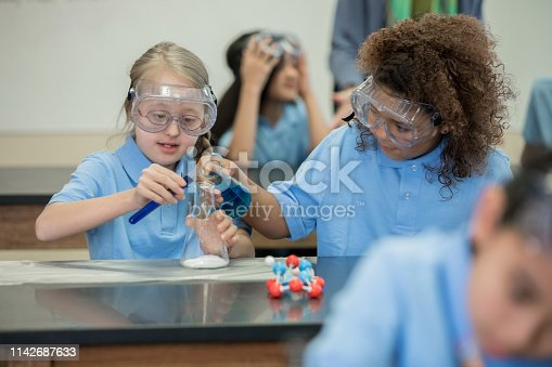 istock Elementary school science student with Down Syndrome does chemistry experiment in lab 1142687633