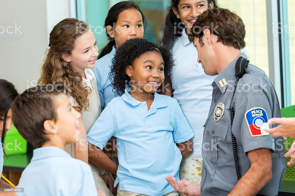 Elementary school student asks policeman a question stock photo