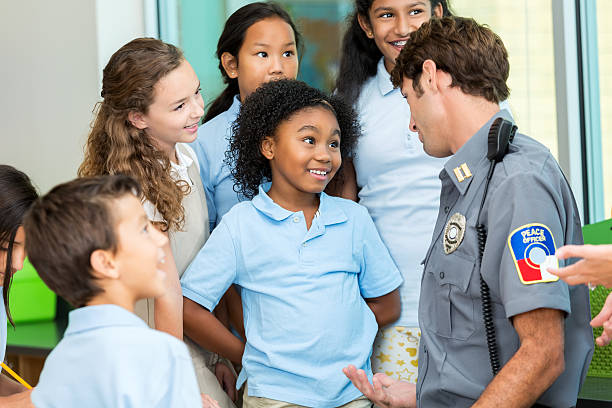 Elementary school student asks policeman a question A diverse group of school children are gathered around a visiting police officer. They are asking him questions about his job. They are attentively listening to the officer speak. The kids are wearing private or charter school uniforms. police meeting stock pictures, royalty-free photos & images