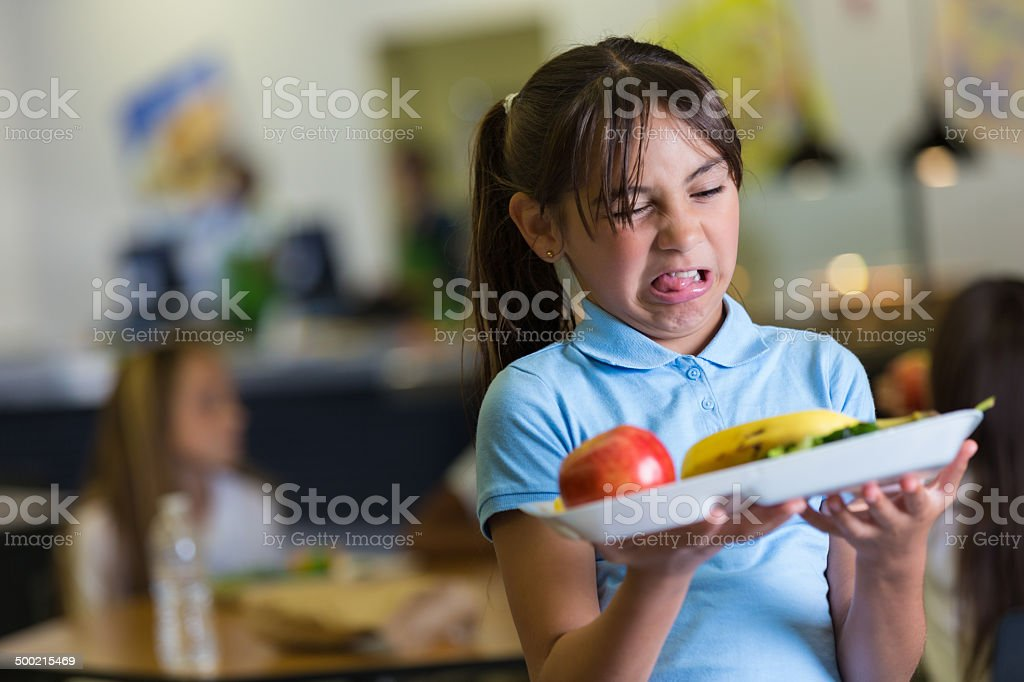 Elementary school student making disgusted face at cafeteria food stock photo
