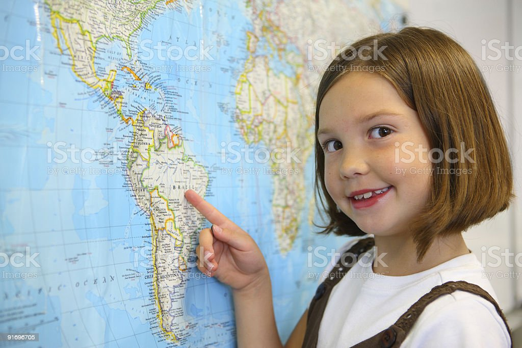 Elementary school student pointing to country on map royalty-free stock photo