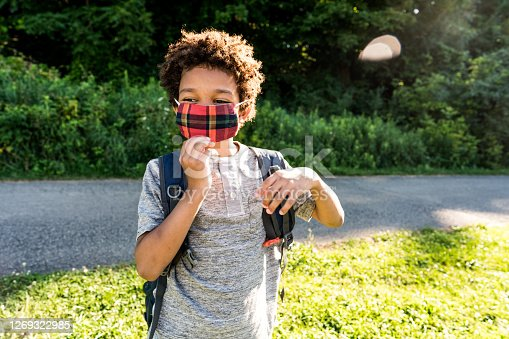 Elementary school student wearing mask outdoor  to help prevent the spread of COVID-19