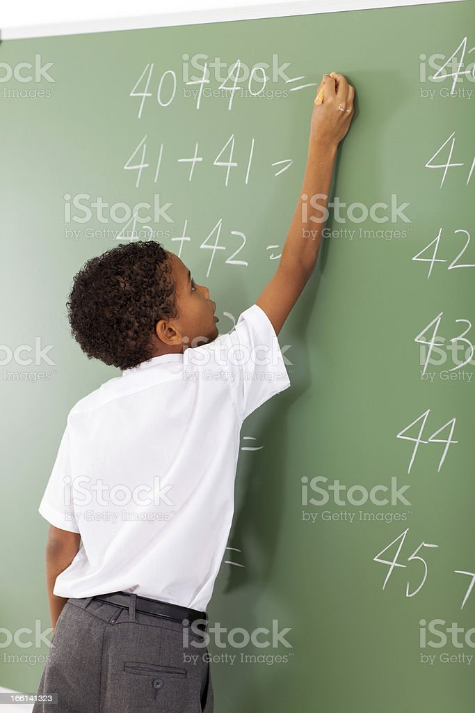 elementary school student writing maths answer stock photo