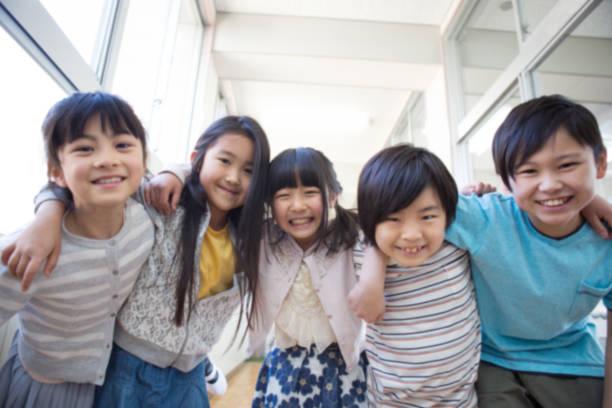 廊下で肩を組む小学生 - 子供時代 ストックフォトと画像