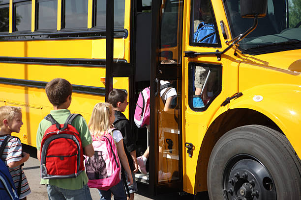 escuela primaria los estudiantes obtienen en autobús - autobuses escolares fotografías e imágenes de stock