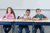 istock Elementary school students in class taking test 521546172