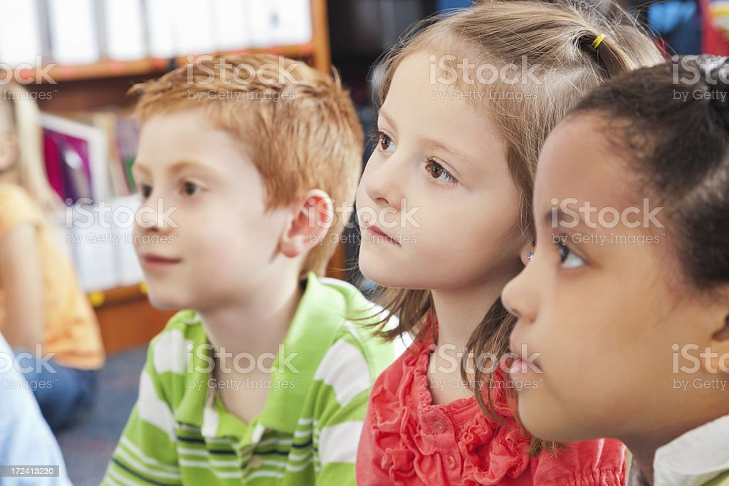 Elementary school students listening to teacher during story time stock photo