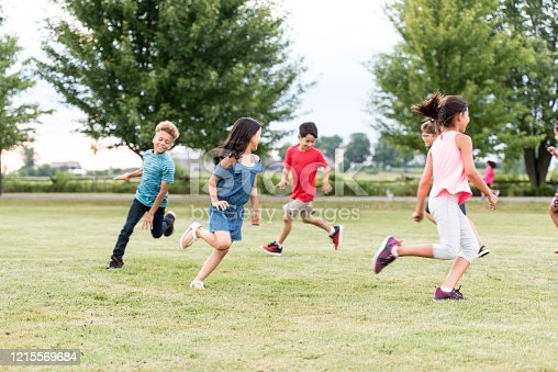 A multi-ethnic group of elementary school students play tag outside at recess.  They are running around the grass outside of the school.