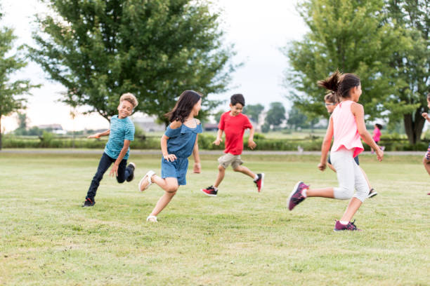 Elementary School Students Play at Recess stock photo A multi-ethnic group of elementary school students play tag outside at recess.  They are running around the grass outside of the school. recess stock pictures, royalty-free photos & images