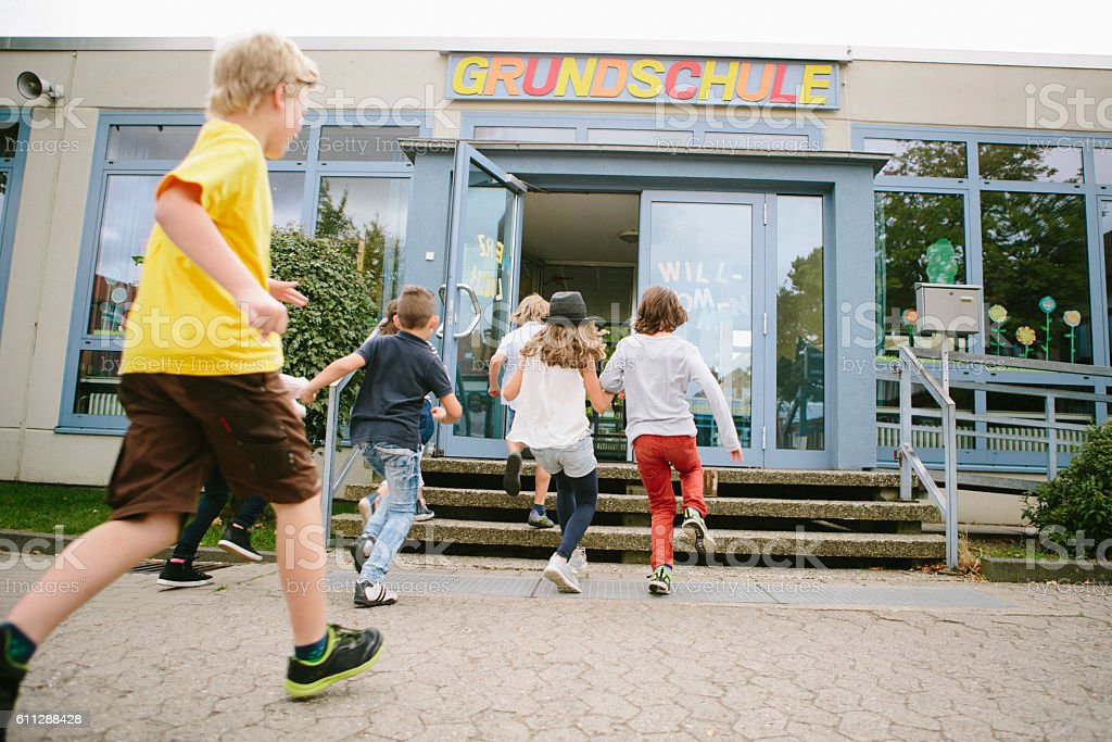 Elementary school students run into school stock photo