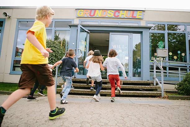 elementary school students run into school - studieren in deutschland stock-fotos und bilder