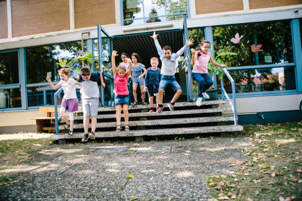 Elementary school students run out of school to Schoolyard stock photo