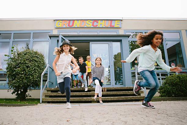 elementary school students run out of school to schoolyard - studieren in deutschland stock-fotos und bilder
