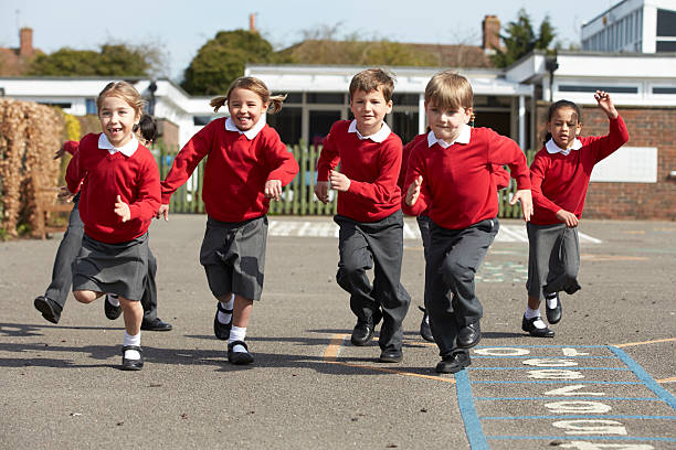 elementary school students running in playground - uniform stock photos and pictures