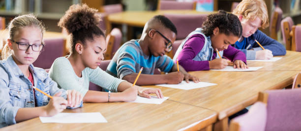 Elementary school students taking a test A group of five multi-ethnic elementary school students sitting in a row at a table, taking a test, writing with pencils on paper. They are 10 and 11 years old. The focus is on the African-American girl 2nd from the left. elementary age stock pictures, royalty-free photos & images