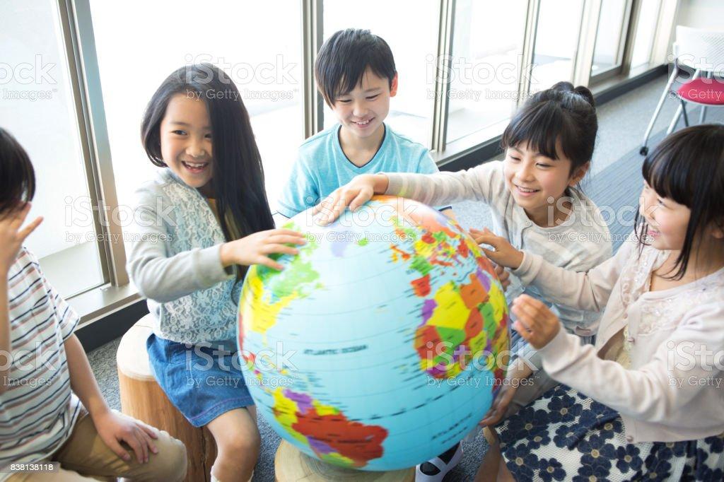 Elementary school students with globe stock photo
