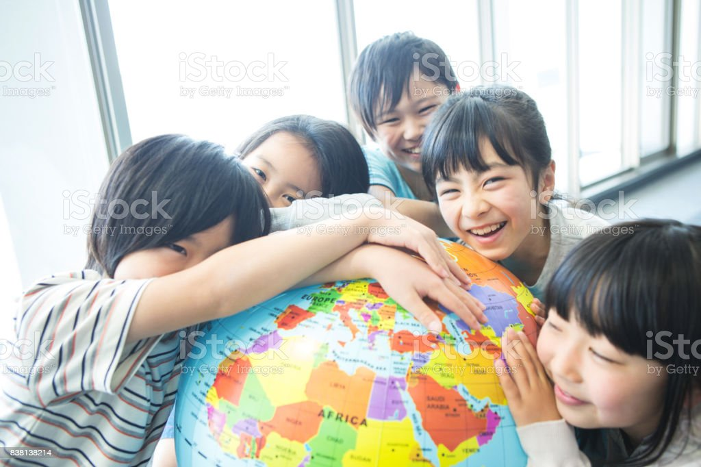 Elementary school students with globe stock photo
