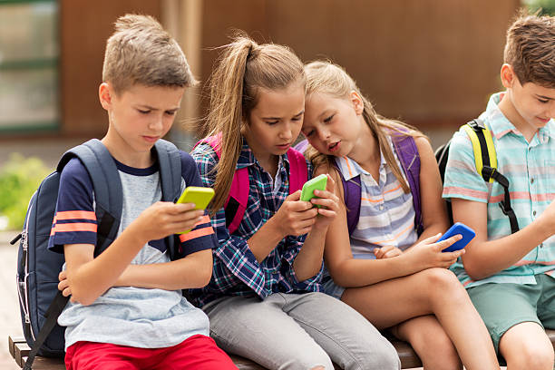 elementary school students with smartphones primary education, friendship, childhood, technology and people concept - group of happy elementary school students with smartphones and backpacks sitting on bench outdoors schoolboy stock pictures, royalty-free photos & images