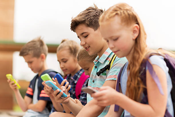 elementary school students with smartphones stock photo